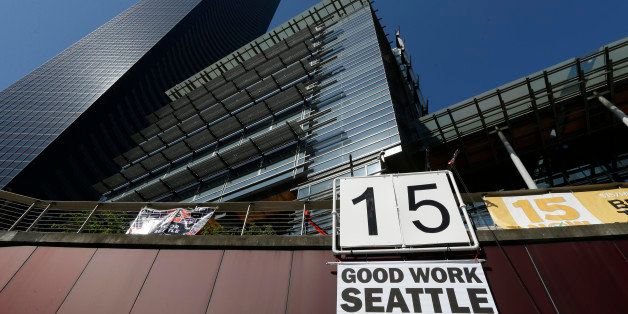 """A sign that reads """"15 Good Work Seattle"""" is displayed below Seattle City Hall, right, and the Columbia Center building, left,"""