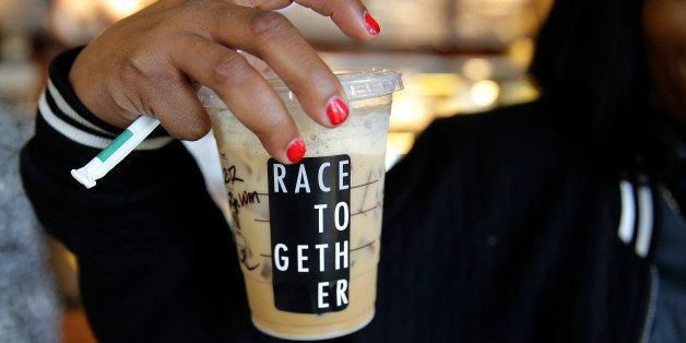 "Larenda Myres holds an iced coffee drink with a ""Race Together"" sticker on it at a Starbucks store in Seattle, Wednesday, Mar"