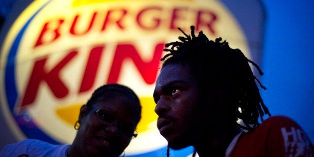 Joshua Collins, right, and Marie Mdamu, talk outside a Burger King restaurant during a protest by fast-food workers calling f