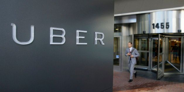 FILE - In this photo taken Tuesday, Dec. 16, 2014, a man leaves the headquarters of Uber in San Francisco. In rulings filed W