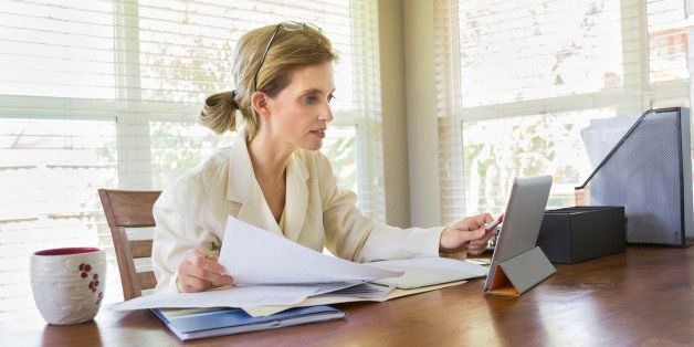 Lifestyle image of a middle-aged woman looking at her tablet while working with documents in her office. Horizontal image