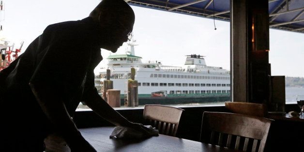 FILE - In this May 14, 2014 file photo, a worker busses a table at Ivar's Acres of Clams restaurant in view of a nearby docke
