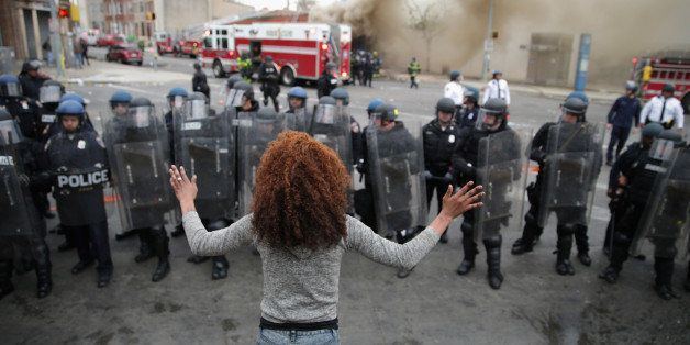 BALTIMORE, MD - APRIL 27:  A woman faces down a line of Baltimore Police officers in riot gear during violent protests follow