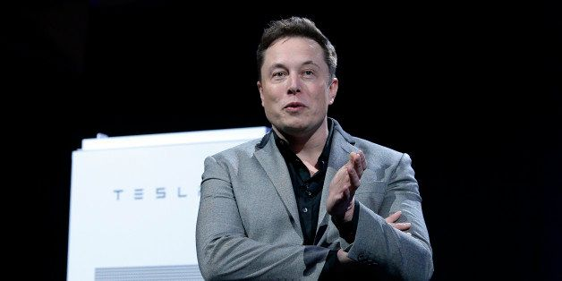 LOS ANGELES, CA - APRIL 30:  Elon Musk, CEO of Tesla, with a Powerpack unit the background unveils suit of batteries for home