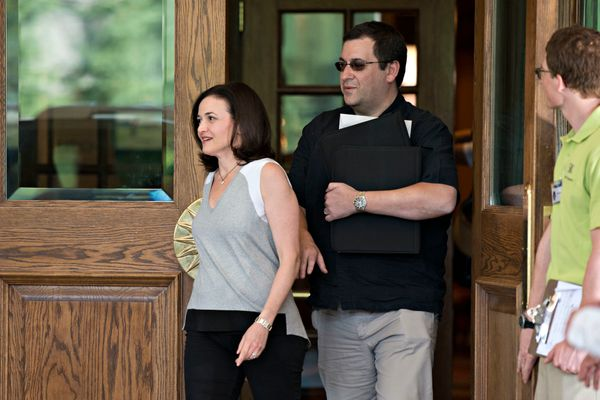 Sheryl Sandberg, chief operating officer of Facebook Inc., left, walks with her husband David 'Dave' Goldberg, chief executiv