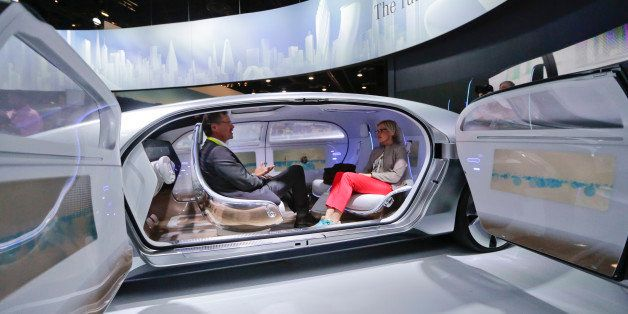 Attendees sit in the self-driving Mercedes-Benz F 015 concept car at the Mercedes-Benz booth at the International CES Tuesday