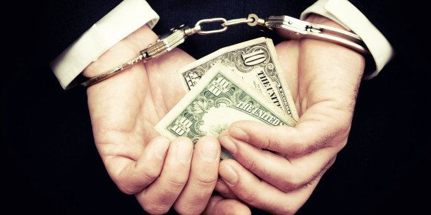 Businessman Hands in Handcuffs Holding Ten Dollar Bill