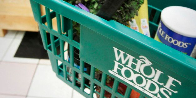 In this photo taken Tuesday, May 11, 2010, a woman carries a basket at a Whole Foods Market, Inc., store in Little Rock, Ark.
