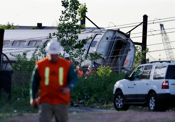 Emergency personnel walk near the scene of a deadly train wreck, Wednesday, May 13, 2015, in Philadelphia. An Amtrak train he