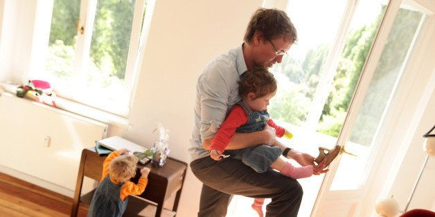 BERLIN - AUGUST 31:  Oliver H., 42, a married federal employee on 6-month paternity leave, puts shoes on his twin 14-month-ol