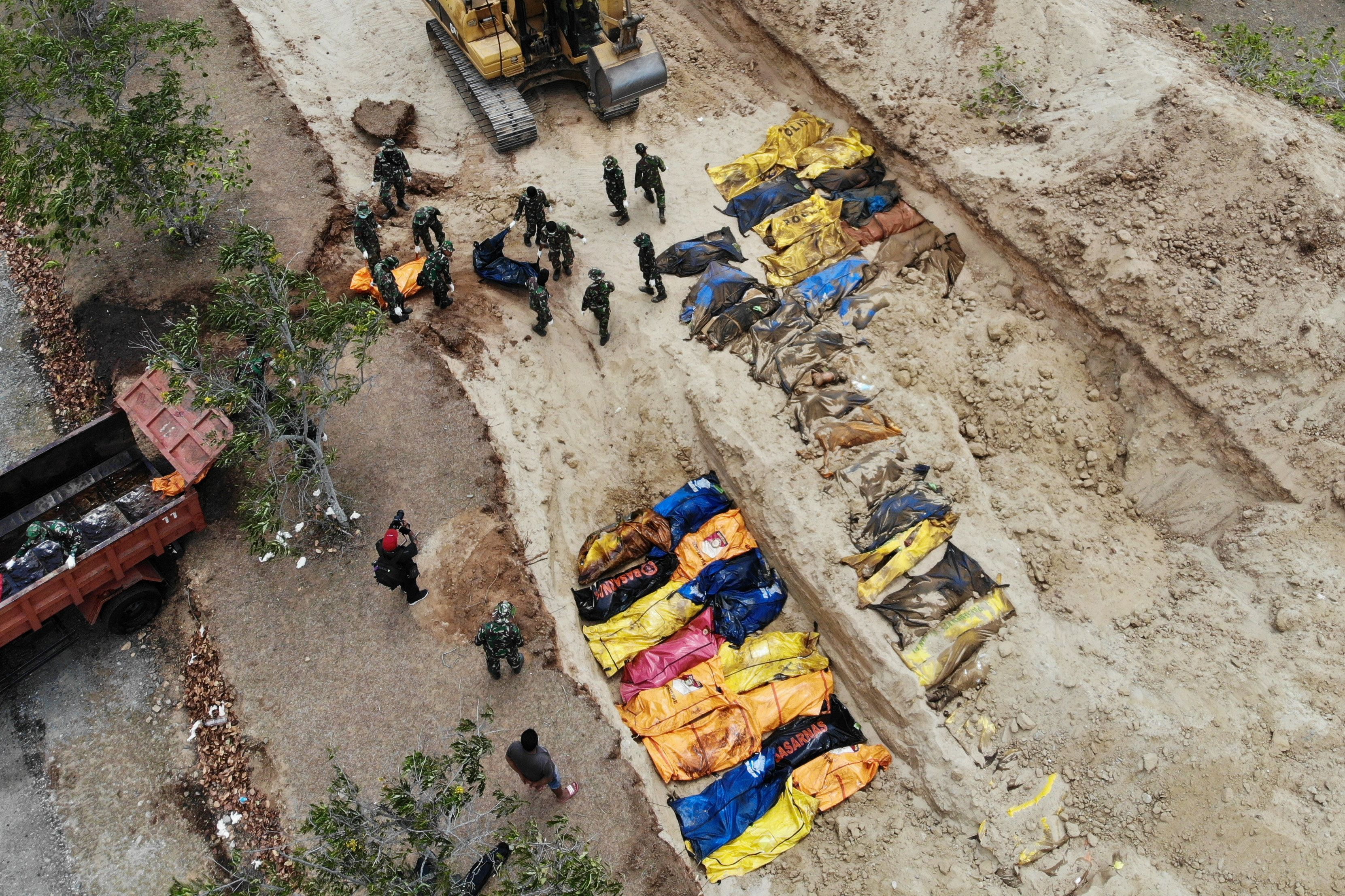 Indonesian soldiers burying quake victims in a mass grave in Poboya in Indonesia's Central Sulawesi on...