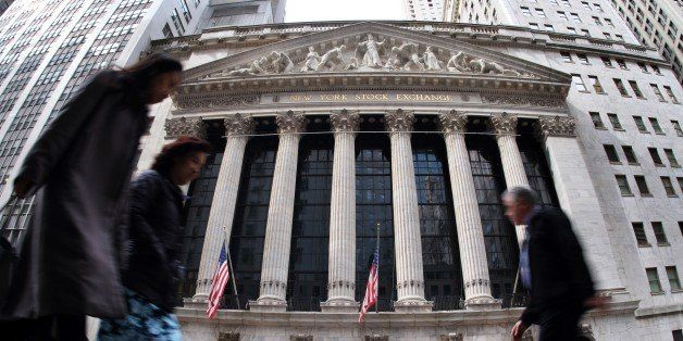 People walk past the New York Stock Exchange (NYSE) building on March 11, 2015 in New York. The average Wall Street bonus ros