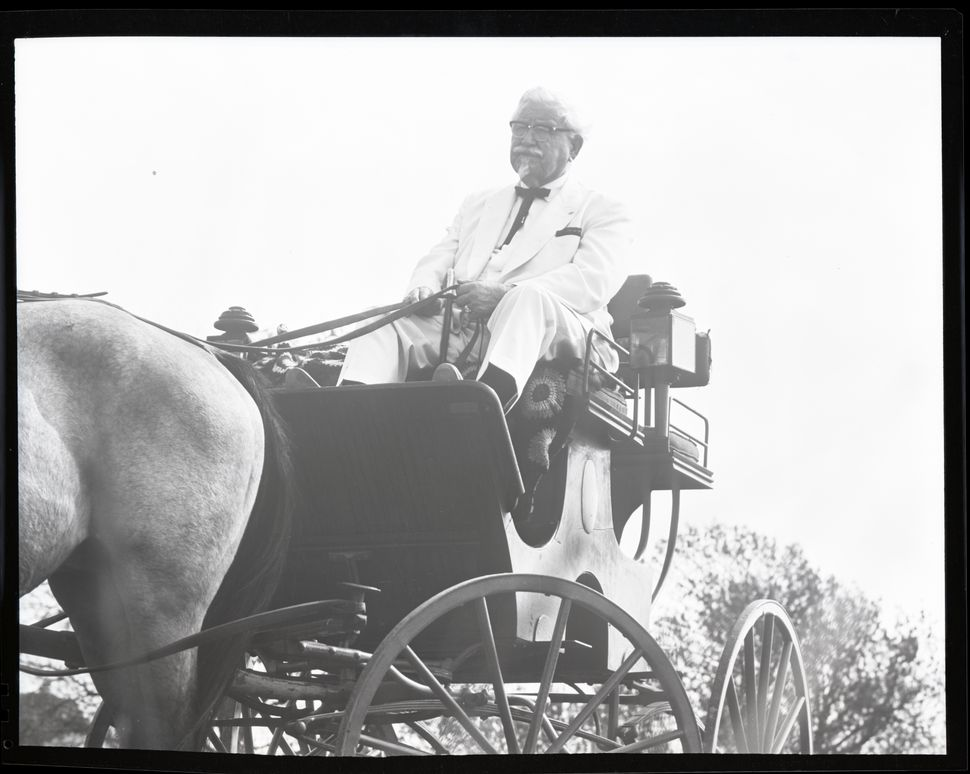 Colonel Sanders rides in a horse and buggy (circa 1960).