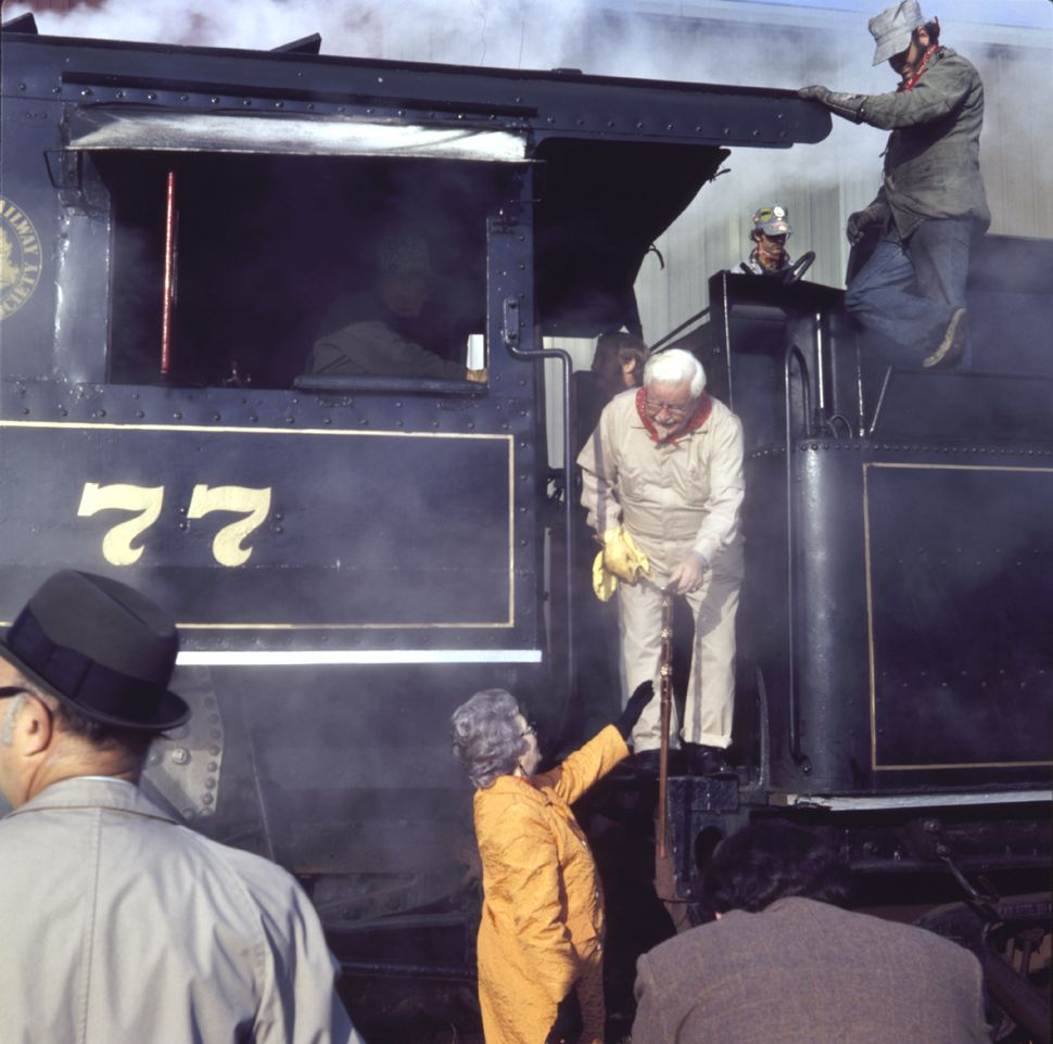 Dressed in a white conductor-style jumpsuit, Colonel Sanders steps off a locomotive with the help of his wife (circa 1960).