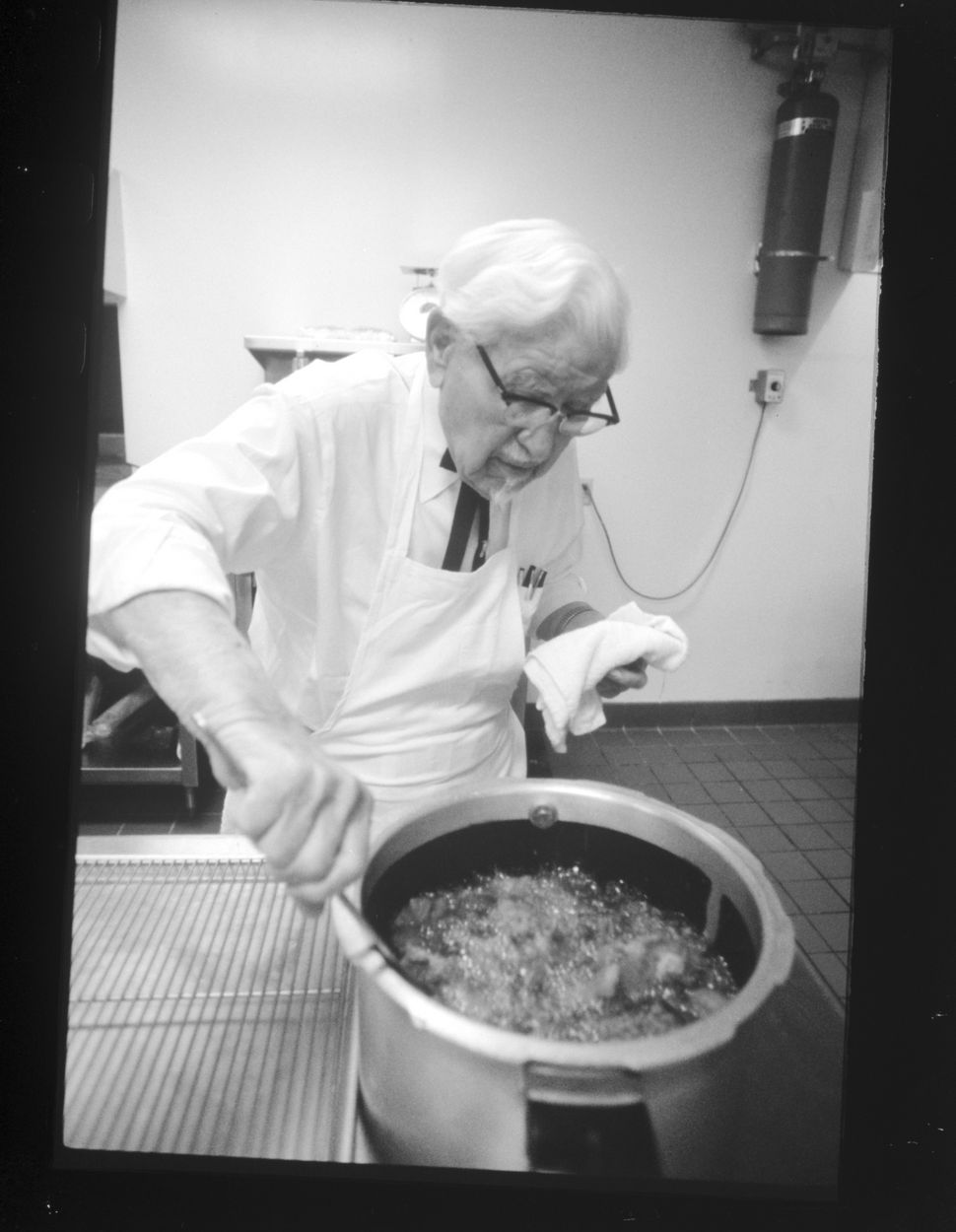 Colonel Sanders oversees his famous Kentucky Fried Chicken as it cooks in the kitchen (circa 1970).