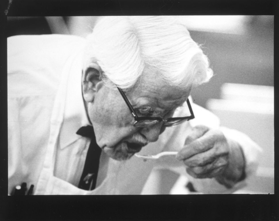 Colonel Sanders taste tests one of his Kentucky Fried Chicken recipes (circa 1970).