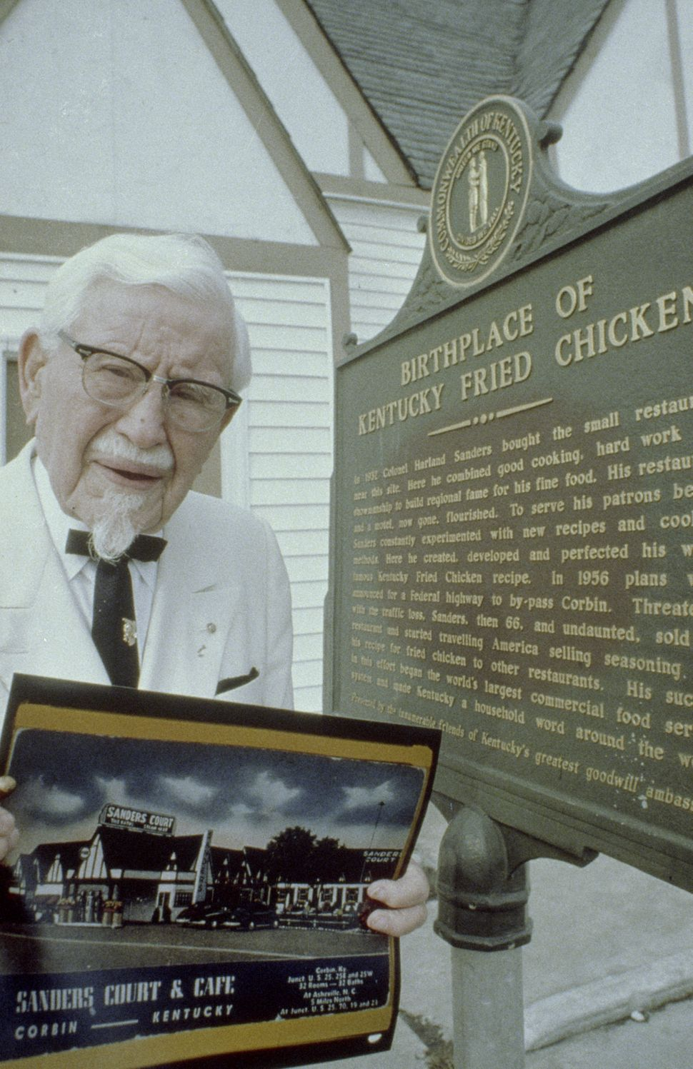"""Colonel Sanders proudly displays photo of Sanders Café next to """"Birthplace of Kentucky Fried Chicken"""" sign (circa 1970)."""