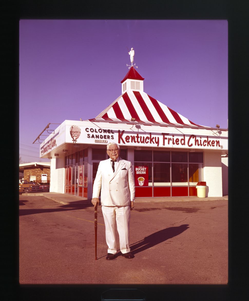 Colonel Sanders stands in front of a Kentucky Fried Chicken restaurant (circa 1960).