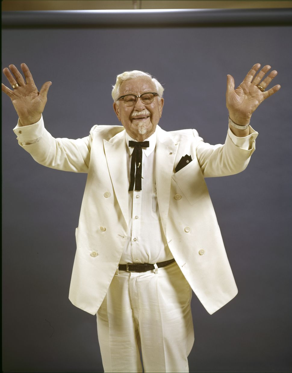 Colonel Sanders poses in his signature white suit with hands raised (circa 1970).