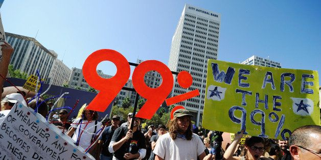 LOS ANGELES, CA - OCTOBER 01:  Protesters hold signs as they march to Los Angeles City Hall during the 'Occupy Los Angeles' d