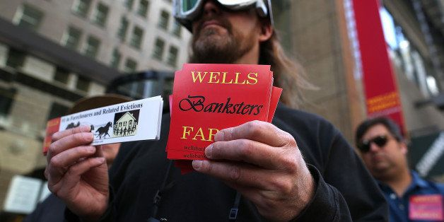 SAN FRANCISCO, CA - APRIL 23:  A protestor holds a sign during a demonstration outside of the Wells Fargo headquarters on Apr
