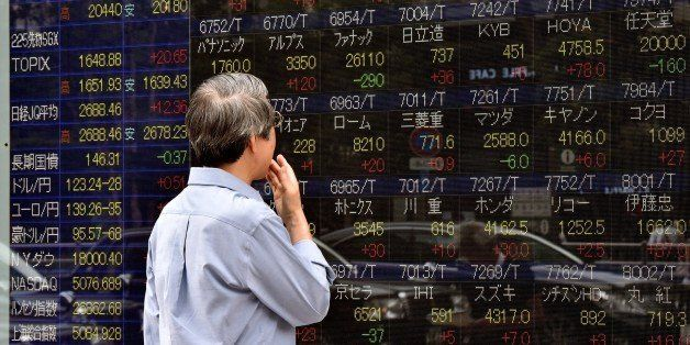 An investor gazes at a share prices board in Tokyo on June 11, 2015. Japan's share prices rose 336.61 points to close at 20,3