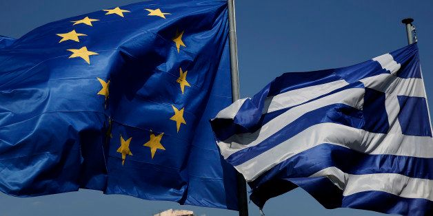 An EU and a Greek flag fly in front of the ancient Parthenon temple, in Athens, on Wednesday, April 9, 2014. Greece announced
