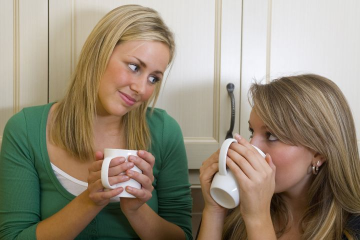 Two beautiful young women chatting over a warm drink.