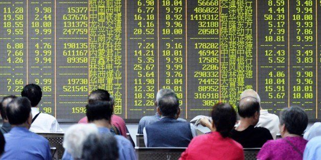 Investors sit in front of a screen showing market movements in a stock firm in Hangzhou, eastern China's Zhejiang province on