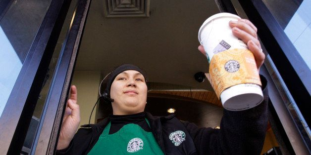 Starbucks barista Alex Igarta hands a coffee drink to a customer from a drive-up window at a store near the company's corpora
