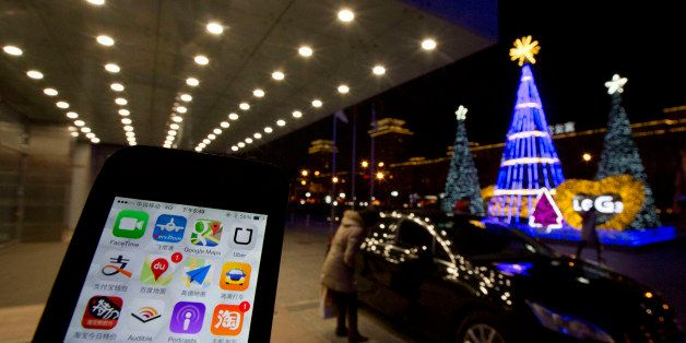 The Uber app is displayed on a phone posed for photos near a woman peering into a car outside a office building in Beijing, F