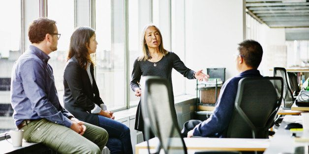 Mature businesswoman leading discussion during team meeting with coworkers in office