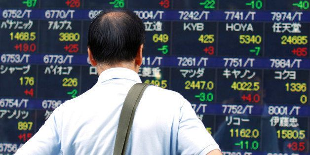 A man looks at an electronic stock indicator of a securities firm in Tokyo, Tuesday, Aug. 11, 2015. Tokyo stocks gave up earl