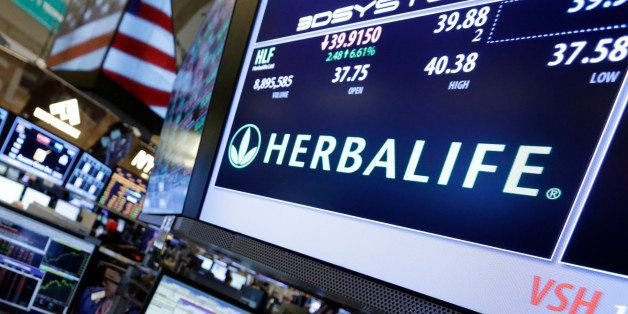FILE - In this Feb. 28, 2013, file photo, a pair of specialists confer at the post that handles Herbalife on the floor of the