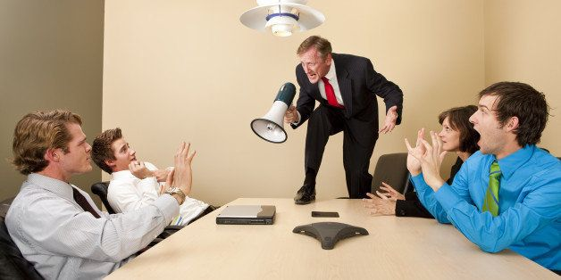 Crazy boss standing on conference table and yelling at employees with megaphone.