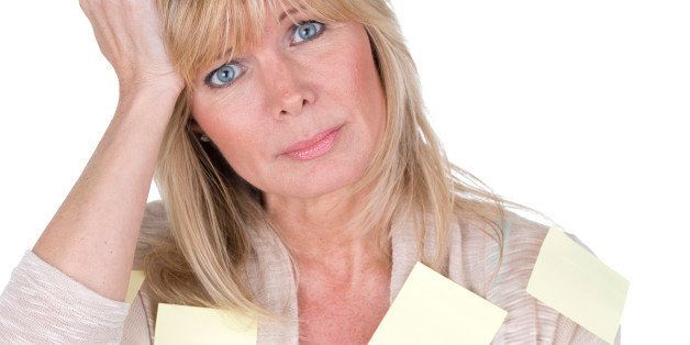 mature woman with post it reminders all over her body as forgetfulness concept