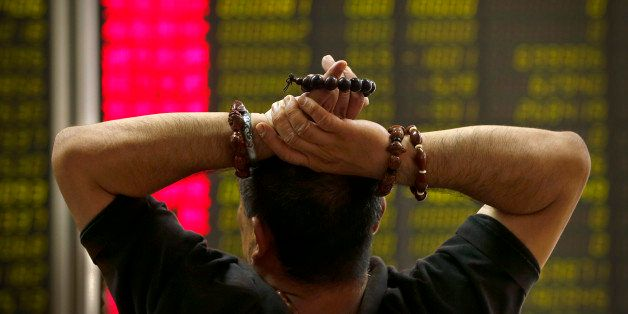 A Chinese investor monitors stock prices at a brokerage house in Beijing, Monday, Aug. 24, 2015. Stocks tumbled across Asia o