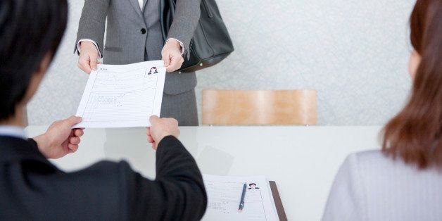 Young Woman Handing Over Her Resume