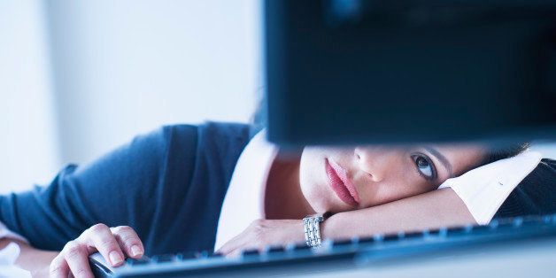 USA, New Jersey, Jersey City, Businesswoman looking tired in front of computer