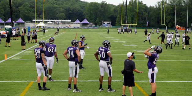 Members of the Baltimore Ravens prepare to run drills at the team's first day of NFL football training camp, Thursday, July 3