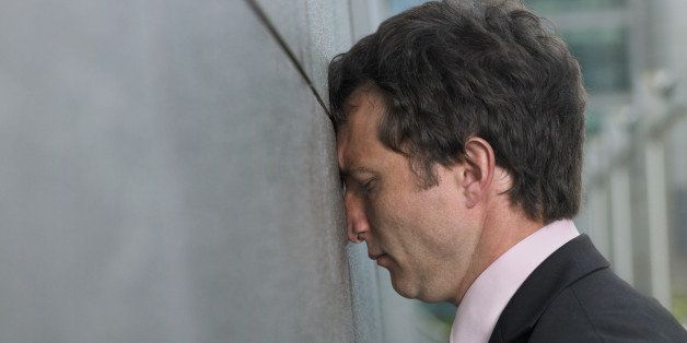 Businessman with face pressed against wall, profile, close-up