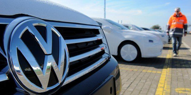 A new Volkswagen (VW) car is seen in the foreground as new cars of the Volkswagen group are parked ready for shipping at the
