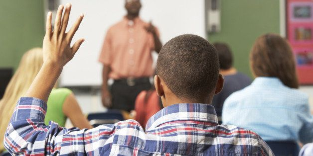 Male Pupil Raising Hand In Class Sitting At Desk