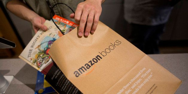 An employee puts books in a bag for a customer at the Amazon Books store in Seattle, Washington, U.S., on Tuesday, Nov. 3, 20