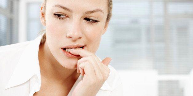 Businesswoman biting fingernails