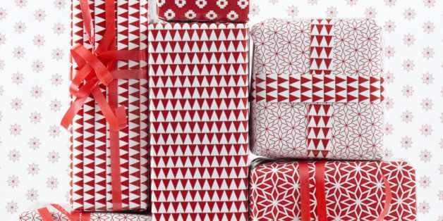 Stack of red patterned wrapped presents, by red patterned background