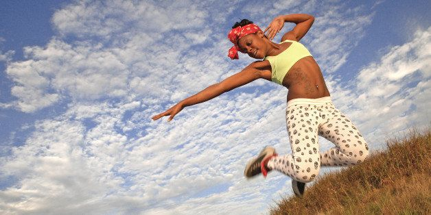 Full length an ecstatic African American female jumping in excitement.