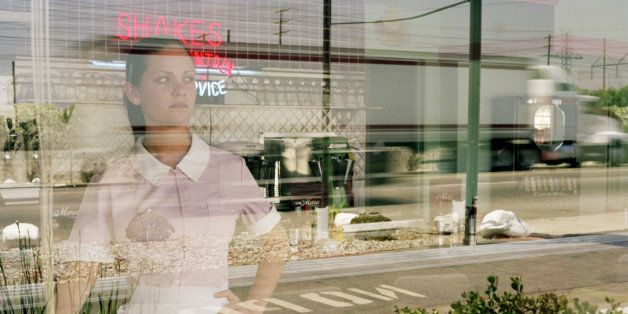 Waitress in diner looking out window