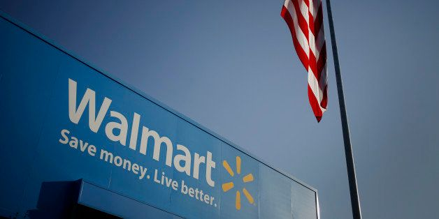 An American flag flies near signage displayed outside of the Wal-Mart Stores Inc. headquarters building in Bentonville, Arkan