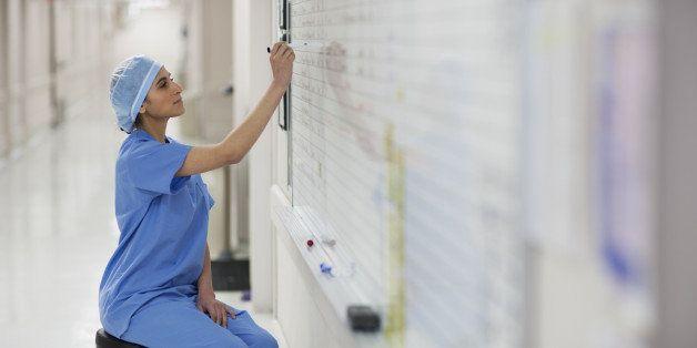 Hispanic nurse writing on whiteboard in hospital
